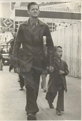 About 1947, Virgil Farmer and his son James downtown Fort Worth on a Saturday. Taken by the street photographer. I was looking up at workers on building girders of a construction site behind the white fence in the background.